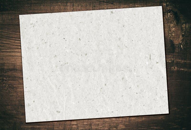 Le papier réutilisé par gris est sur le conseil en bois grunge image libre de droits