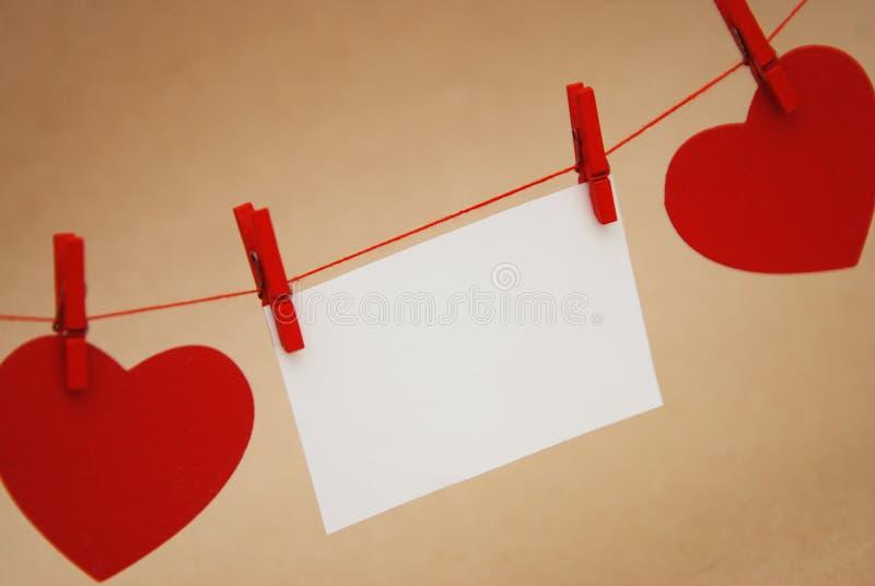 Le papier rouge de coeurs a coupé avec Mini Clothes Pin et le papier blanc blanc pour le texte, fond neutre Image de jour de vale photos libres de droits