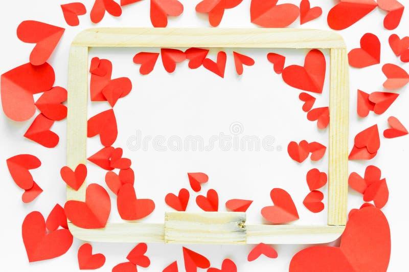 Le papier rouge a formé le coeur autour du tableau blanc sur le backg d'isolement par blanc photo stock