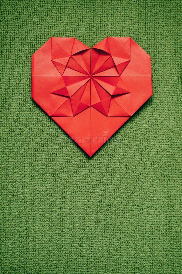 Le papier rouge a plié le coeur fait main d'origami sur le fond gentil tricoté vert de chandail Calibre vertical confortable de c photographie stock