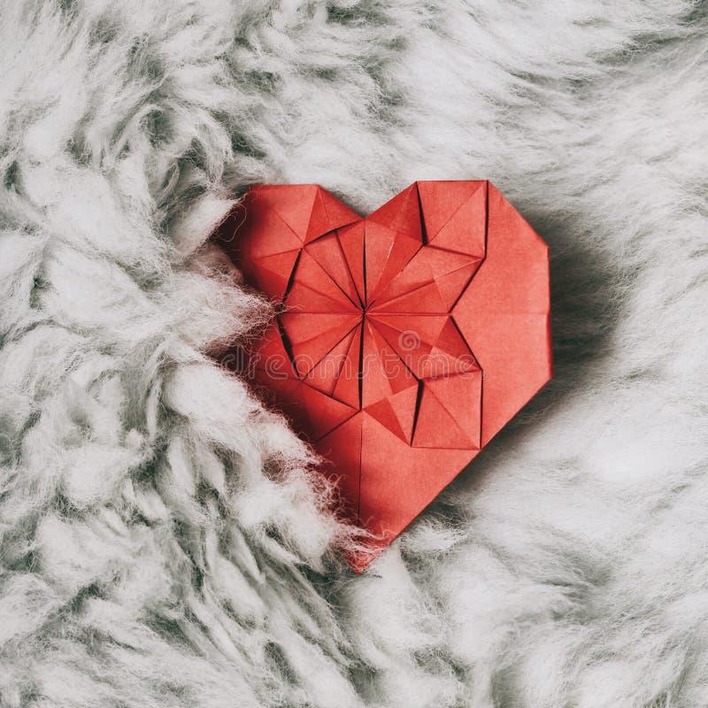 Le papier rouge a plié le coeur fait main d'origami sur le fond pelucheux naturel blanc de fourrure Calibre vertical confortable  image libre de droits