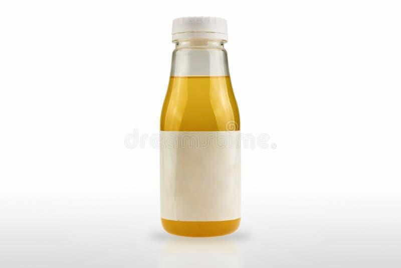 Le paquet en plastique de bouteille contenant le produit a un label blanc d'isolement sur le fond blanc images libres de droits