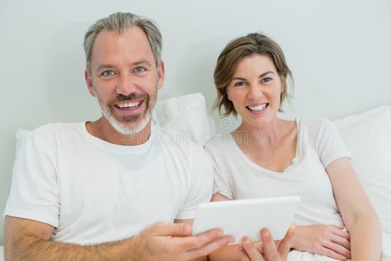 Le par genom att använda den digitala minnestavlan på säng i sovrum hemma arkivfoto