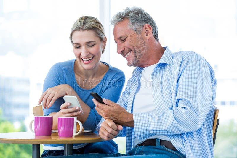 Le par genom att använda mobiltelefoner på kafét royaltyfri fotografi