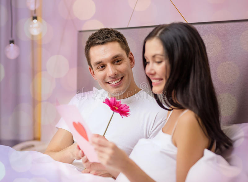 Le par i säng med vykortet och blomman arkivbild
