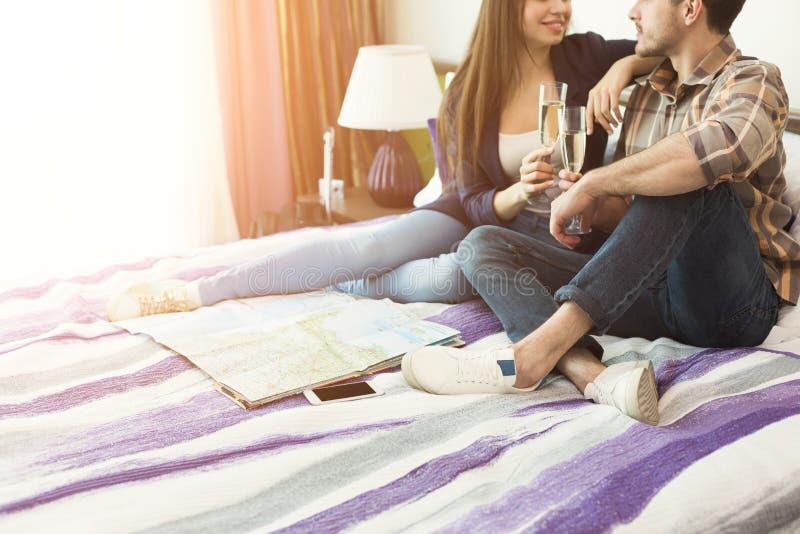 Le par med champagneexponeringsglas i säng arkivbilder