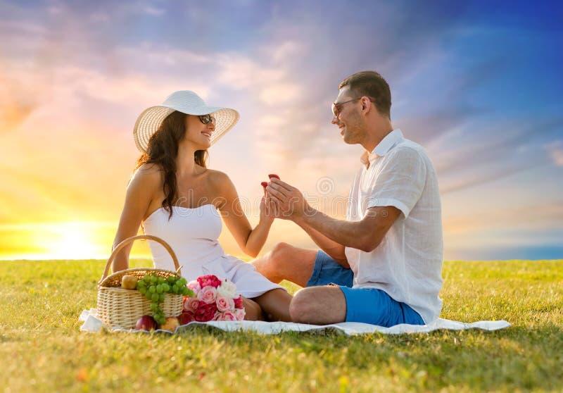 Le par med den lilla röda gåvaasken på picknicken fotografering för bildbyråer