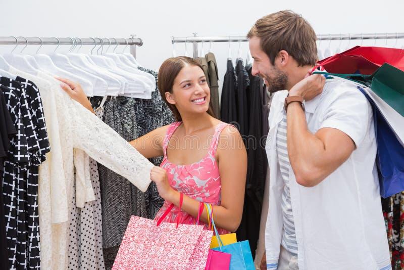 Le par med shoppingpåsar som ser kläder royaltyfri foto