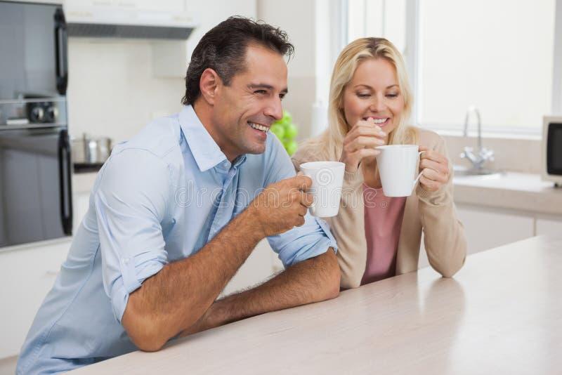 Le par som dricker kaffe i kök royaltyfri fotografi