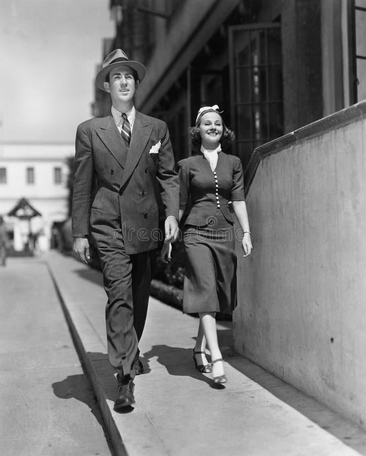 Le par som går på trottoaren (alla visade personer inte är längre uppehälle, och inget gods finns Leverantörgarantier som royaltyfria foton