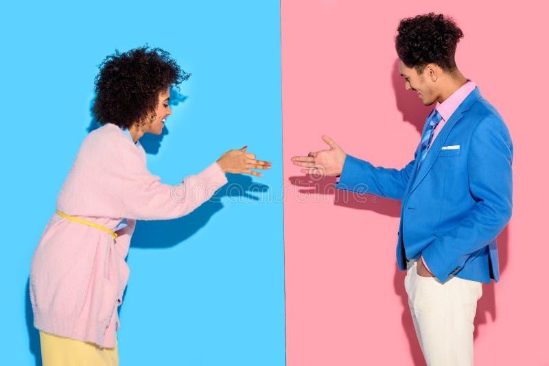 Le par som gör en gest och gör roliga skuggor på rosa färger och blått royaltyfria foton