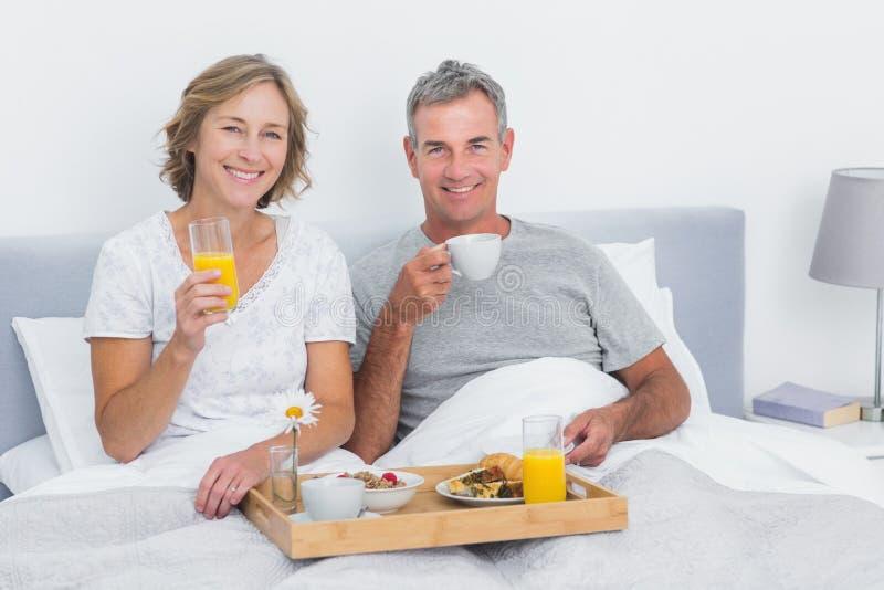 Le par som har frukosten i säng tillsammans royaltyfri foto