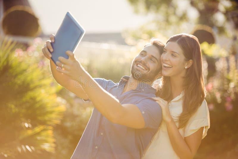 Le par som klickar selfie med den digitala minnestavlan arkivbilder