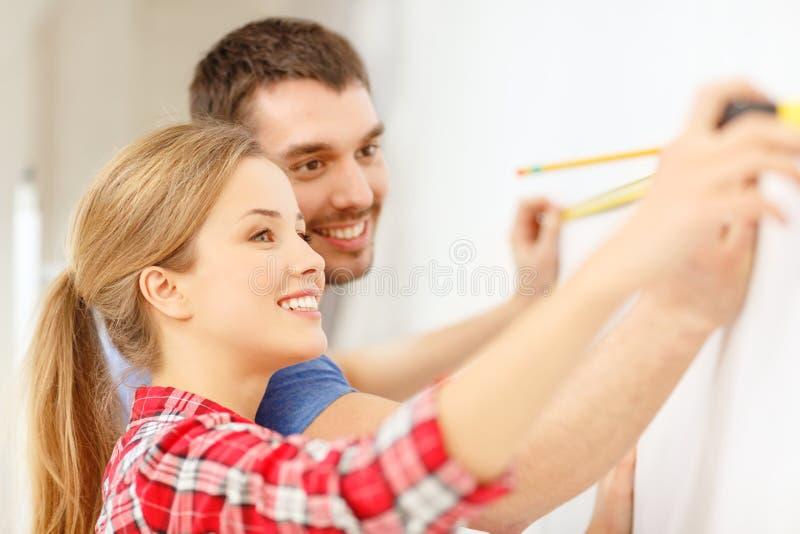 Le par som mäter väggen royaltyfria foton