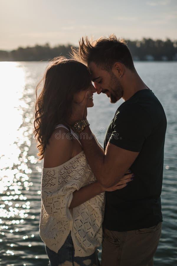 Le par som trycker på huvud vid floden i solnedgång royaltyfri fotografi