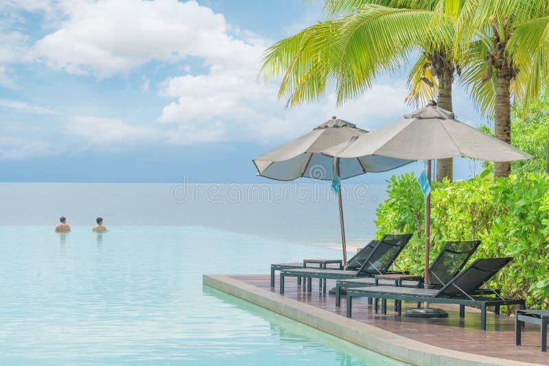 Le parapluie et la chaise avec la piscine dans l'hôtel recourent image stock