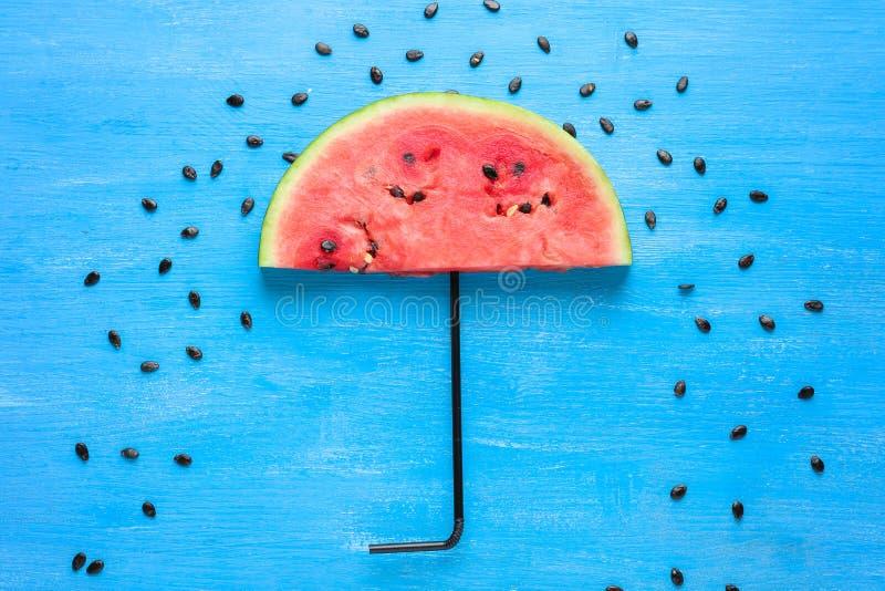 Le parapluie a fait de la tranche fraîche de pastèque sur le fond de couleur photo libre de droits