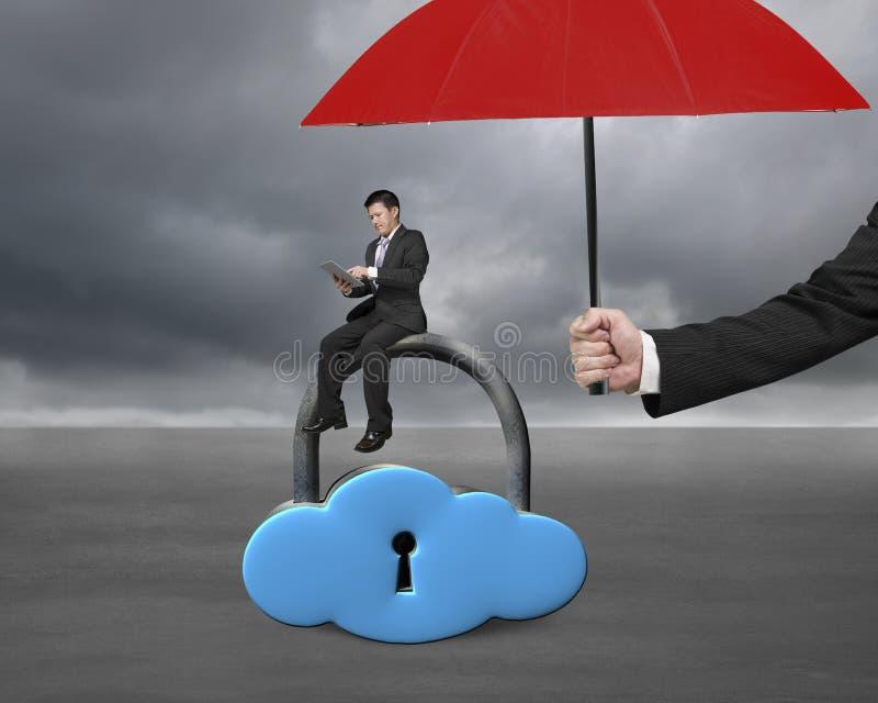 Le parapluie rouge protègent l'homme d'affaires utilisant le comprimé sur la serrure de nuage photographie stock libre de droits