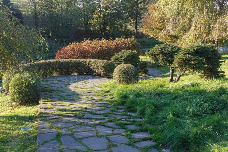 Le parc avec la pelouse verte, arbres a équilibré les buissons et le chemin en pierre naturel photos libres de droits