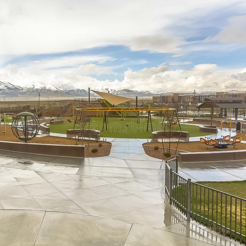 Le parc carré avec la vue du vaste ciel nuageux au-dessus de la neige a fait une pointe la montagne et les maisons images libres de droits