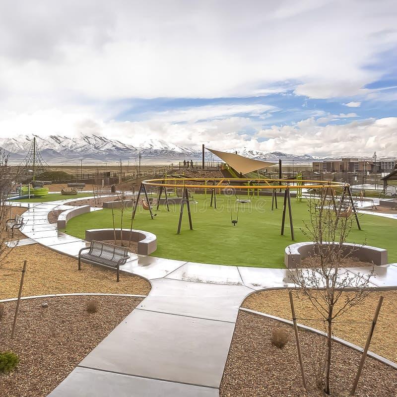 Le parc carré de cadre avec la vue de la neige éloignée a couvert la montagne sous le ciel bleu et les nuages épais photographie stock