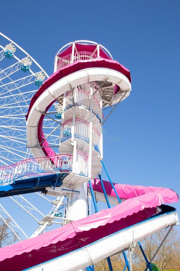 Le parc d'attractions avec des ferris de fêtes foraines roulent dedans le ciel bleu photographie stock libre de droits