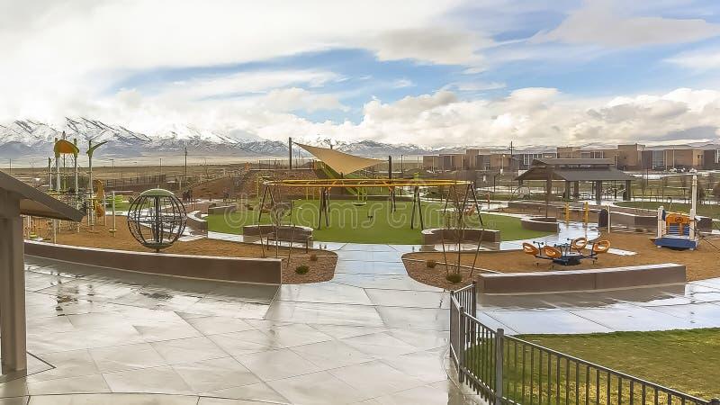 Le parc de panorama avec la vue du vaste ciel nuageux au-dessus de la neige a fait une pointe la montagne et les maisons image libre de droits