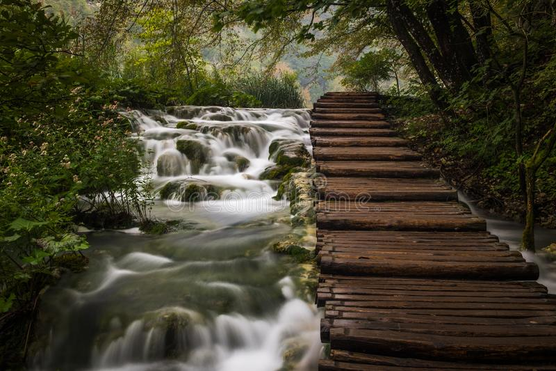 Le parc national de beau et renversant lac Plitvice, Croatie, fin vers le haut de tir d'une cascade avec la large promenade du cô images libres de droits