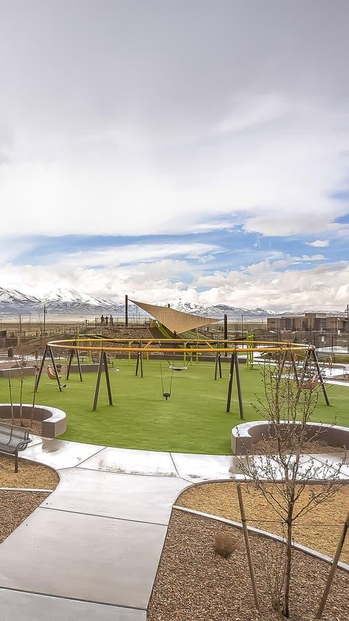 Le parc vertical avec la vue de la neige éloignée a couvert la montagne sous le ciel bleu et les nuages épais photos stock