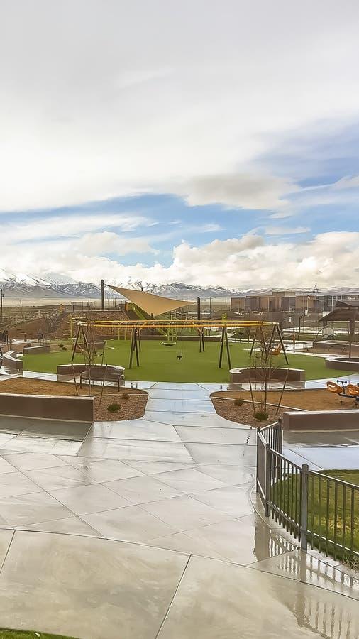Le parc vertical avec la vue du vaste ciel nuageux au-dessus de la neige a fait une pointe la montagne et les maisons images libres de droits
