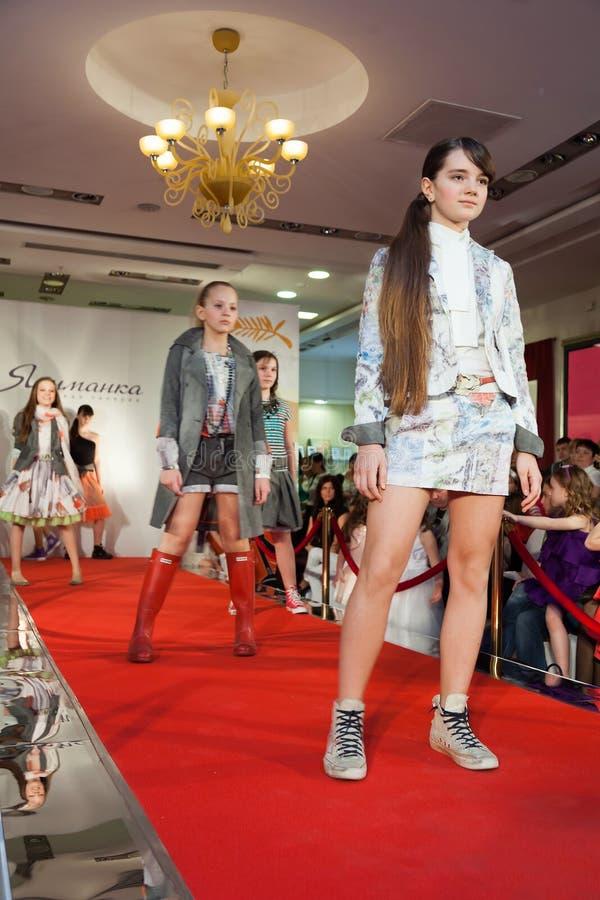 Le parecchie ragazze sulla pista ad una sfilata di moda fotografie stock