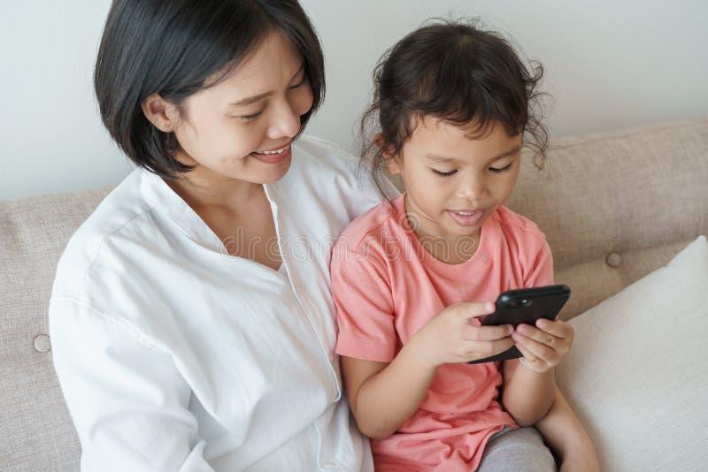 Le parent et la fille utilisent le téléphone pour observer des médias en ligne images stock
