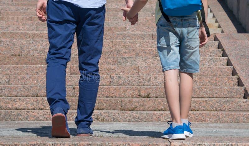 Le parent mène un étudiant à l'école, vue arrière contre un contexte des escaliers photographie stock