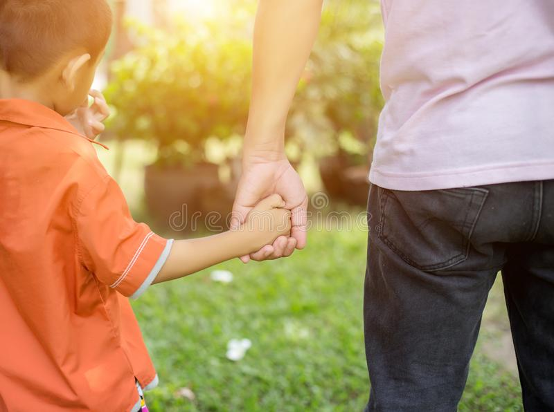 Le parent tient la main d'un petit enfant images libres de droits
