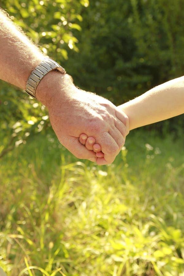 Le parent tient la main d'un petit enfant photos libres de droits