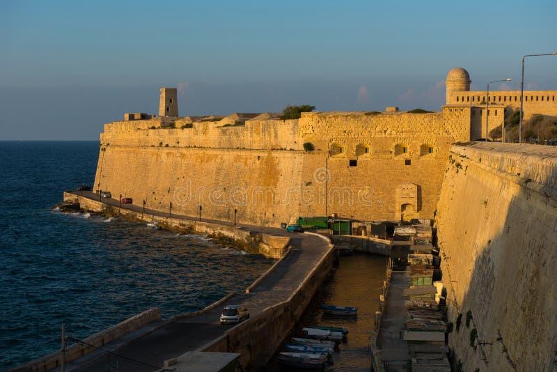 Le pareti antiche della fortificazione di La Valletta nella sera si accende immagini stock libere da diritti
