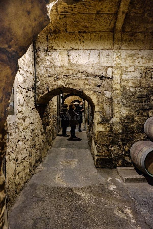 Le pareti di pietra ed i tunnel di comunicazione fra le cantine di pietra sotterranee in cui il vino di La Rioja invecchia in vec immagine stock