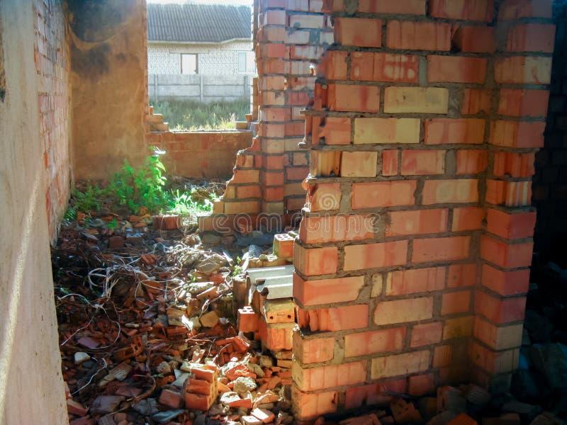 Le pareti interne distrutte di una casa vuota di mattoni immagine stock