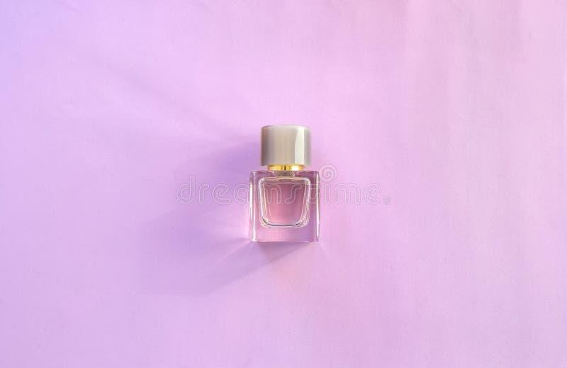Le parfum des femmes dans la bouteille en verre sur le fond rose Vue sup?rieure, configuration plate photographie stock libre de droits