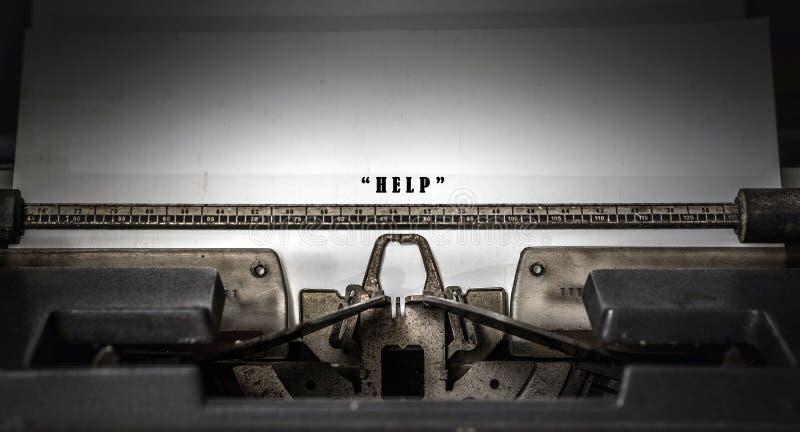 Le parole del ` di AIUTO del ` hanno scritto su una macchina da scrivere d'annata in bianco e nero immagine stock