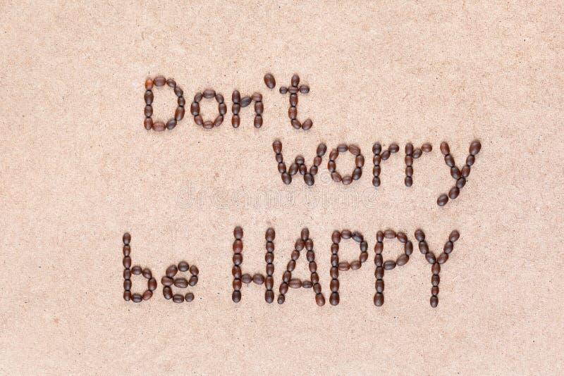 Le parole non si preoccupano per essere felice scritte con i chicchi di caff?, colpo da sopra immagini stock libere da diritti