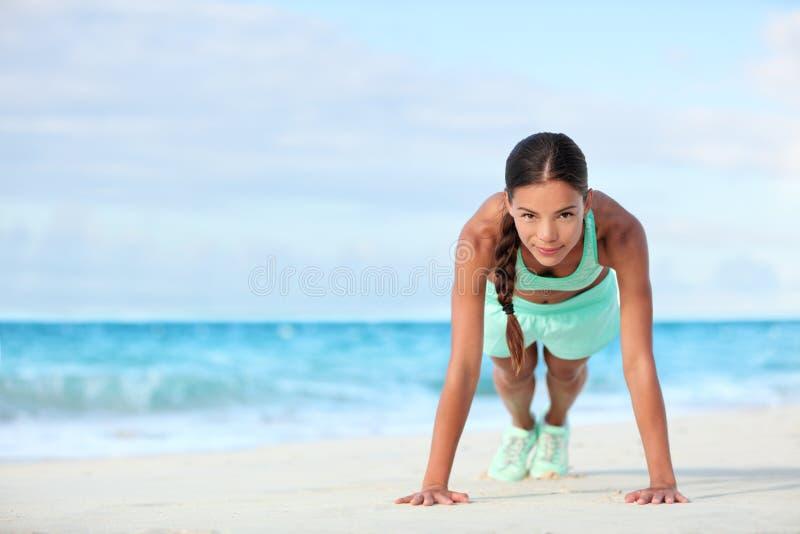 Le parquet de sourire de femme de plage de forme physique faisant le noyau de pose de planche de yoga s'exerce images stock