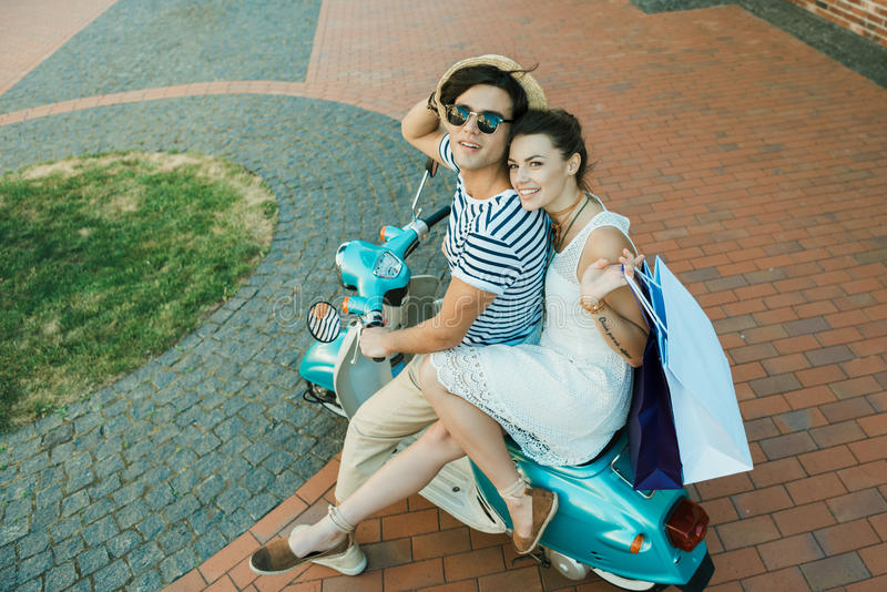Le parridning på sparkcykel- och innehavshoppingpåsar utomhus royaltyfri fotografi