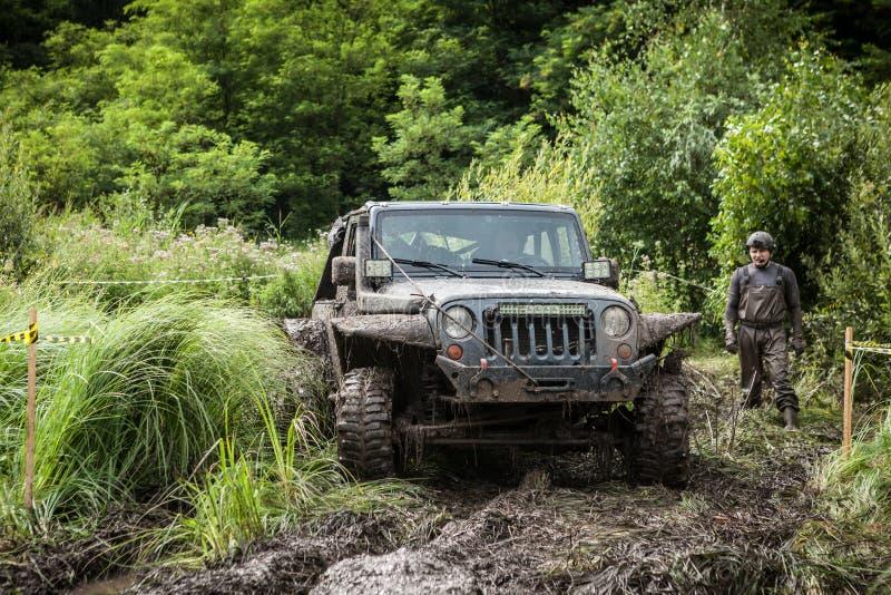 Le participant sur la jeep passe un puits boueux profond images libres de droits