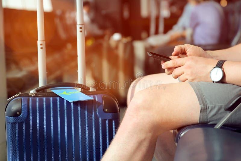 Le passager attend le vol retardé à l'aéroport/utilisant le téléphone portable image stock