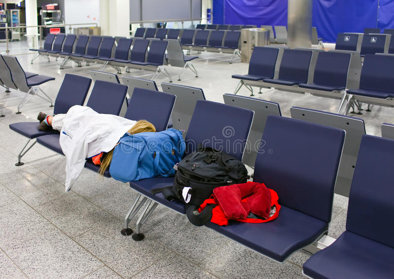 Le passager dort dans un aéroport vide de nuit après l'annulation de vol photos stock
