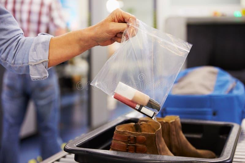Le passager met des liquides dans le sac au contrôle de sécurité dans les aéroports photos stock