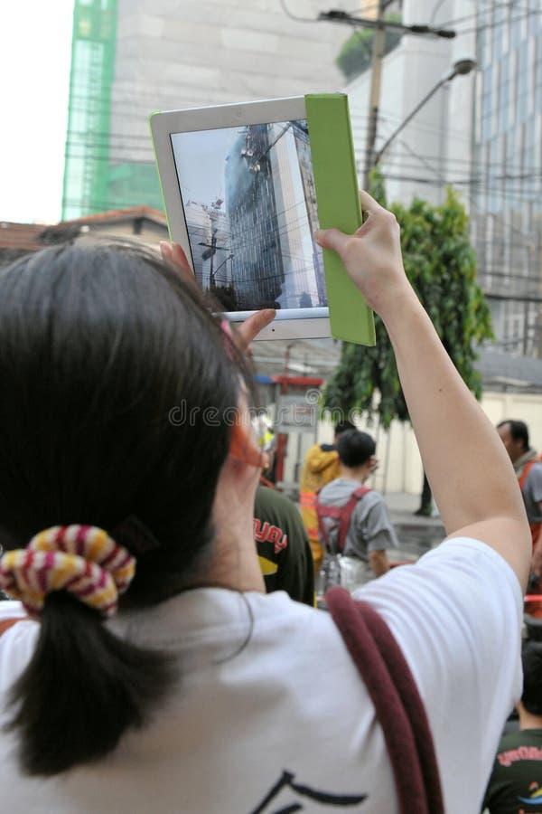Le passant utilise près une tablette à l'incendie de bureau de photo images stock