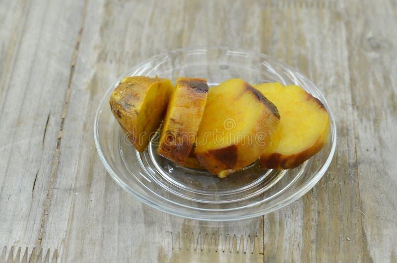 Le patate dolci cotte hanno tagliato le fette sul piatto su fondo di legno immagine stock libera da diritti