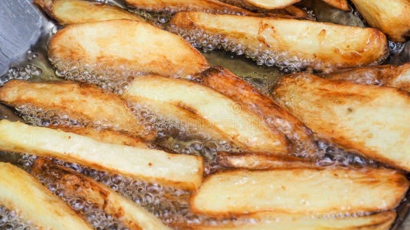 Le patate fritte è bruciatura che cucina in pentola dell'acciaio inossidabile zummano fotografie stock